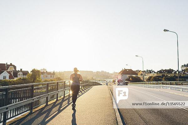 Schweden  Blekinge  Karlskrona  Junge Frau beim Joggen auf der Brücke