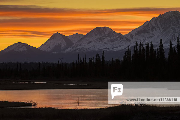 'Sunrise over the pond and mountains along the Parks Highway in autumn  near Cantwell in interior Alaska; Alaska  United States of America'