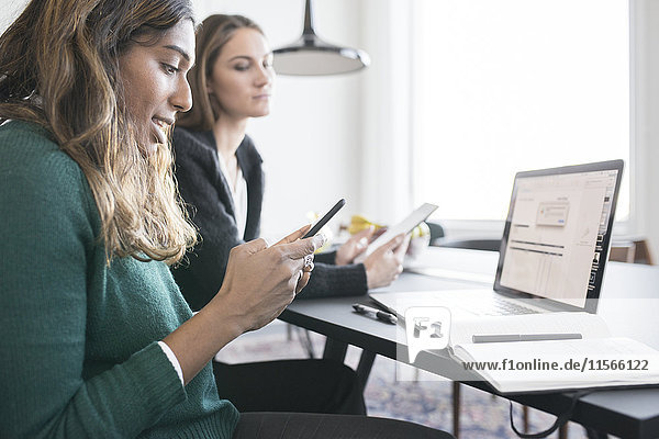Two businesswomen in office using cell phones and laptop
