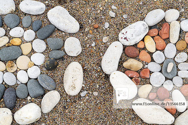 'Close up of designs made with various coloured rocks in the sand on the beach; South Shields  Tyne and Wear  England'