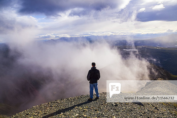 'A man watches clouds swirling beside a ridge high in the Alaska Range; Alaska  United States of America'