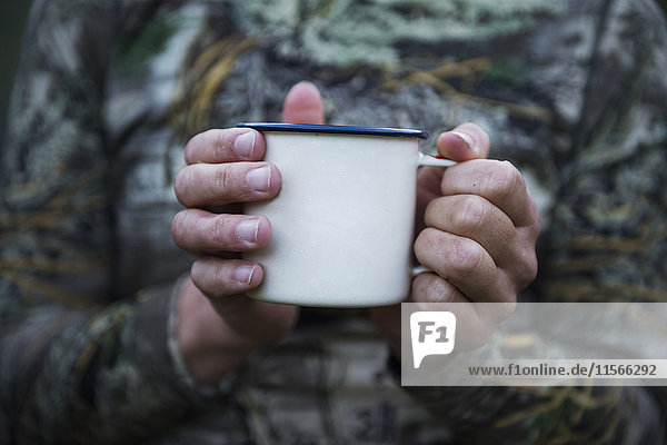 Hands holding metal cup