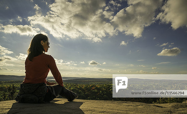 'Woman sitting on a cliff overlooking Algonquin Park; Ontario  Canada'