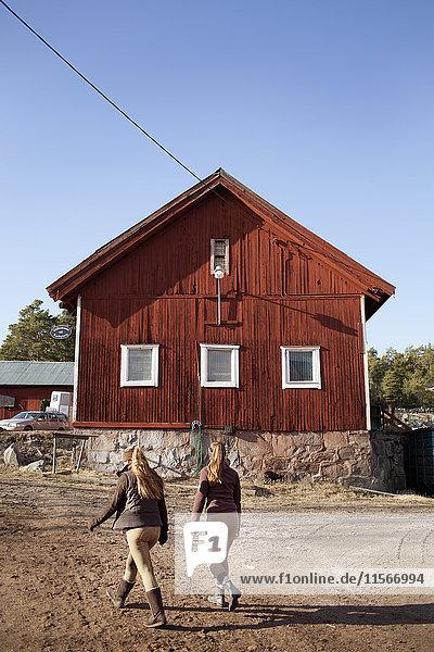 Schweden  Uppland  Faringso  Junge Reiterinnen auf dem Bauernhof