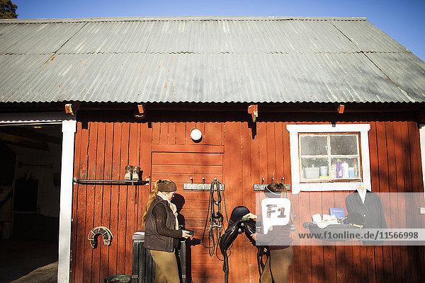 Schweden  Uppland  Faringso  Frauen vor der Scheune stehend