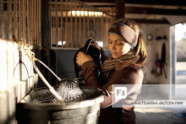 Schweden  Uppland  Faringso  Frau gießt Wasser aus Gießkanne in Eimer