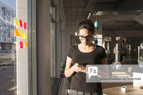 Woman using smartphone by office window