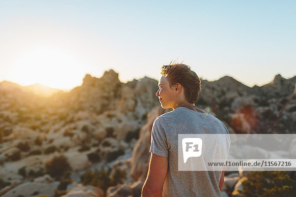 USA  Kalifornien  Joshua Tree National Park  Junger Mann  der bei Sonnenuntergang nachdenkt.