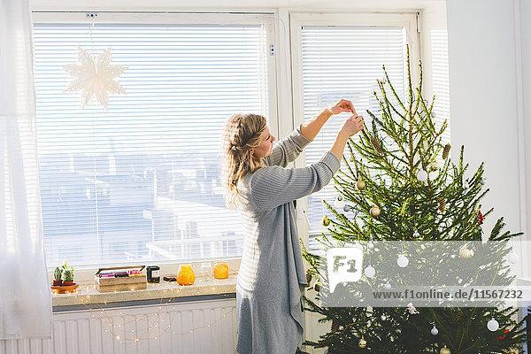 Finnland  Helsinki  Frau schmückt Weihnachtsbaum