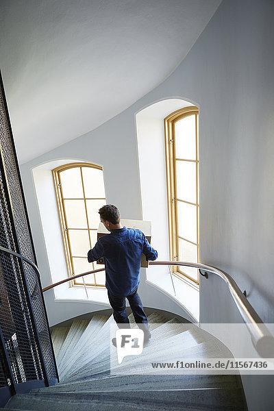 Schweden  Mann geht auf Stufen  Tragkasten