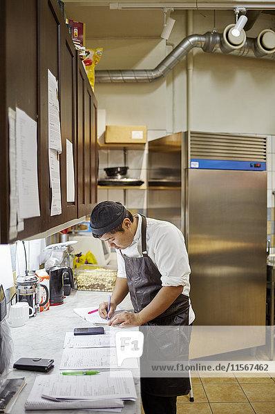 Schweden  Mann in der Schürze schreibt in der Küche