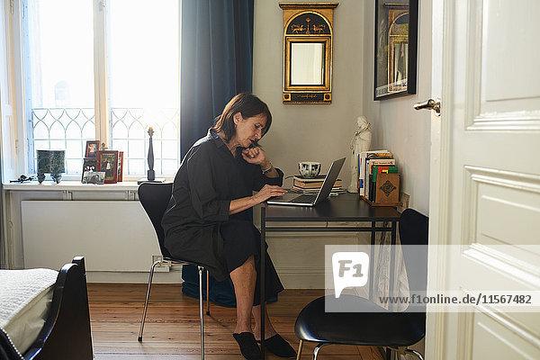 Schweden  Frau in schwarzem Kleid mit Laptop zu Hause