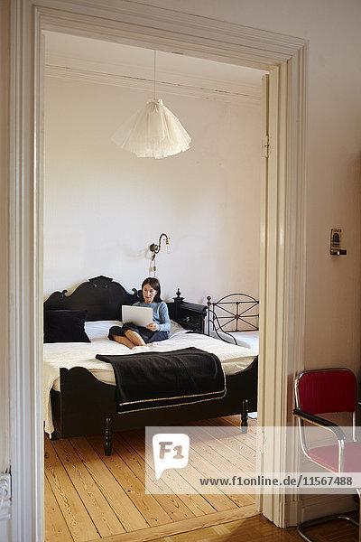 Schweden  Frau mit Laptop im Bett sitzend