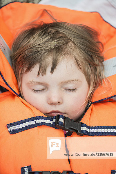 Boy sleeping in life vest