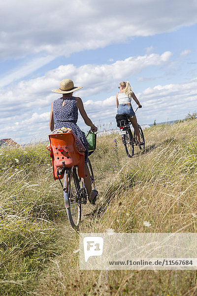 Women riding bicycles in field