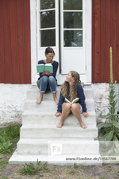 Mother with daughter reading on stairs