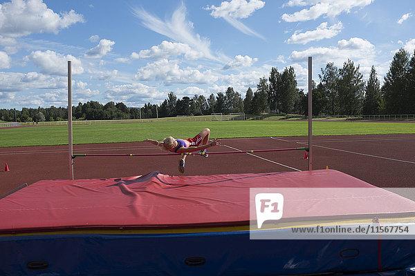 Teenage girl jumping over pole