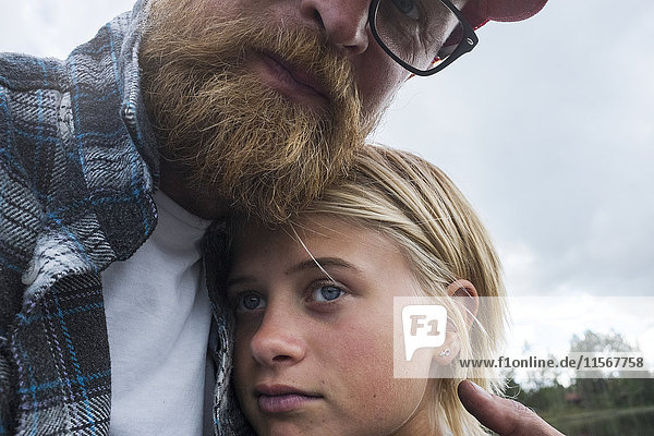 Portrait of father embracing daughter