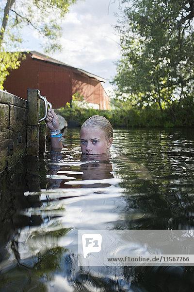 Teenage girl swimming by jetty