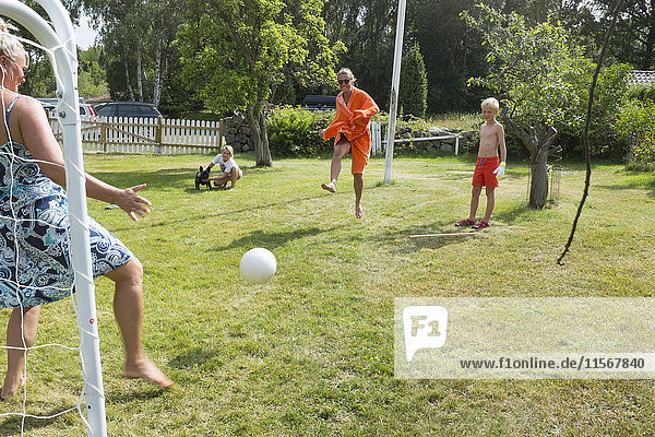 Family playing soccer in garden