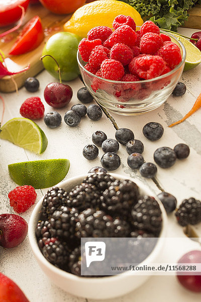 Raspberries in bowl surrounded by other fruits