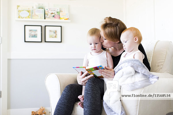 Mother and sons (12-17 months) reading picture book