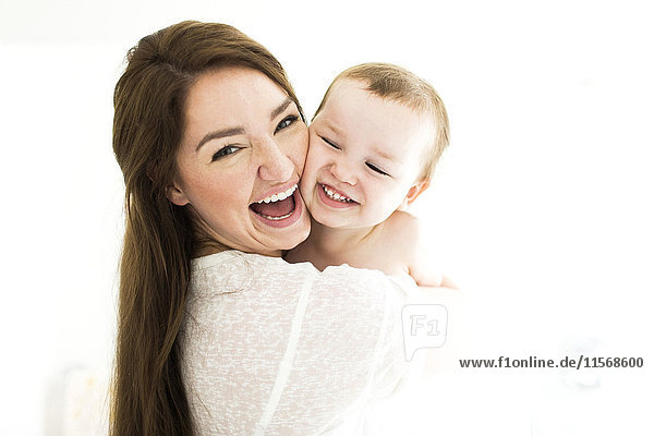 Mother carrying son (4-5) and laughing