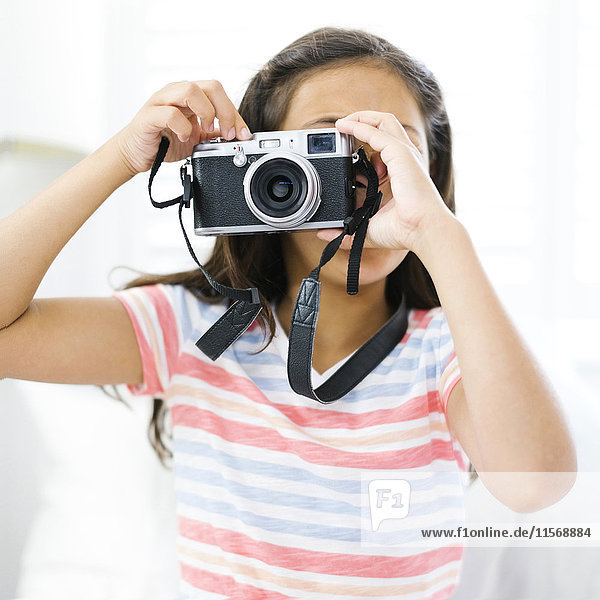 Girl (10-11) holding camera and taking photo