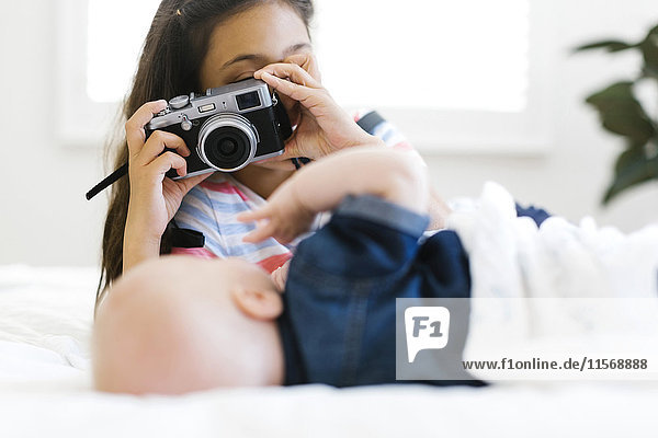 Girl(10-11) taking photo of her small brother (12-17 months) lying on bed