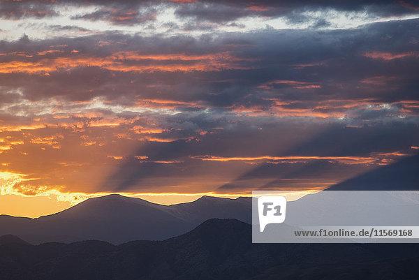 USA  Colorado  Denver  Setting sun shining through clouds over Front Range
