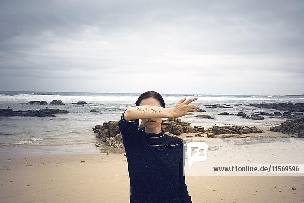 Frau mit aufgemalten geschlossenen Augen auf dem Arm steht am Strand  hinten Meer  Südafrika