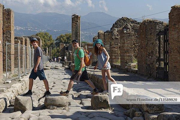 Vater und Kinder laufen über historische Steine  Via Stabiana  antike Stadt  Pompeji  Kampanien  Italien  Europa