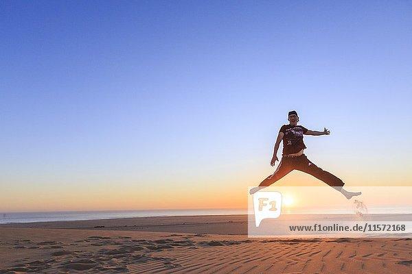 Junger Mann springt fröhlich in die Luft  Sonnenuntergang  Namib Wüste  Langstrand  Swakopmund  Region Erongo  Namibia  Afrika