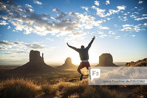 Junger Mann springt  Sonnenaufgang  Tafelberge West Mitten Butte  East Mitten Butte  Merrick Butte  Monument Valley  Navajo Tribal Park  Navajo Nation Reservation  Arizona  Utah  USA  Nordamerika Junger Mann springt, Sonnenaufgang, Tafelberge West Mitten Butte, East Mitten Butte, Merrick Butte, Monument Valley, Navajo Tribal Park, Navajo Nation Reservation, Arizona, Utah, USA, Nordamerika