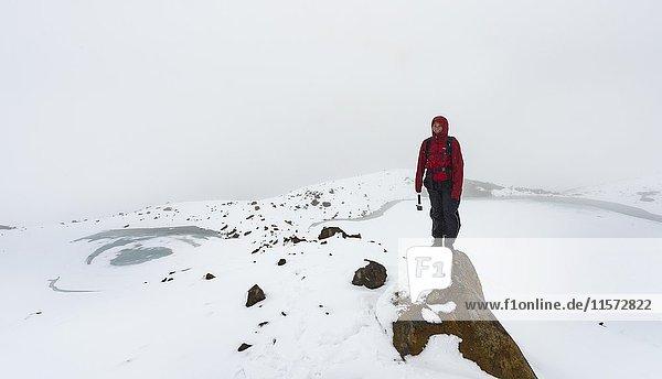 Wanderin steht auf Felsen  Zugefrorene Emerald Lakes  Tongariro Alpine Crossing mit Schnee  Tongariro National Park  Südinsel  Neuseeland  Ozeanien