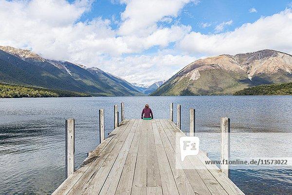 Frau sitzt auf Steg  Ausblick auf Lake Rotoiti  Nelson Lakes National Park  Tasman District  Südinsel  Neuseeland  Ozeanien