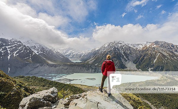 Hiker standing on rocks  view into the Hooker Valley from Sealy Tarns Track  glacial lakes Mueller Lake and Hooker Lake  Mount Cook National Park  Canterbury Region  South Island  New Zealand  Oceania