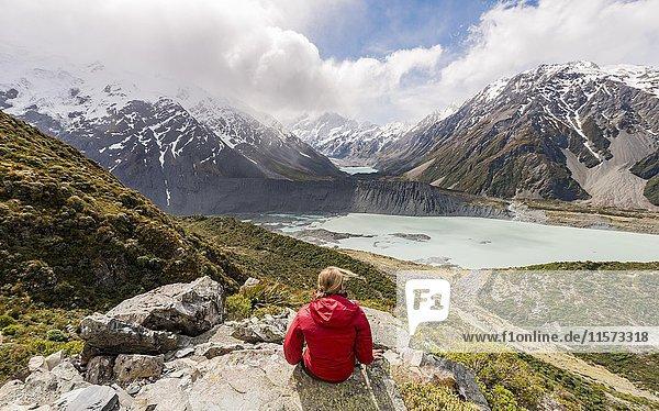 Wanderin sitzt auf Felsen  Ausblick in das Hooker Valley vom Sealy Tarns Track  Gletscherseen Mueller Lake und Hooker Lake  Mount Cook Nationalpark  Canterbury  Südinsel  Neuseeland  Ozeanien