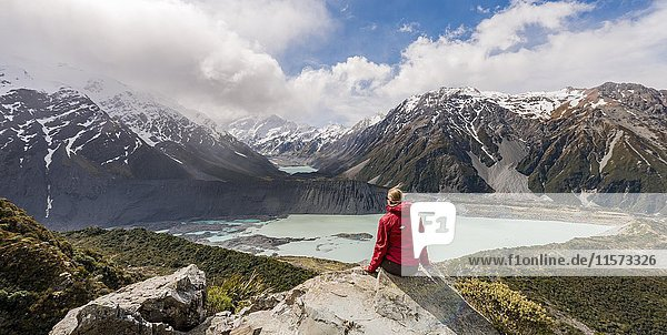 Hiker sitting on rocks  view into the Hooker Valley from Sealy Tarns Track  glacial lakes Mueller Lake and Hooker Lake  Mount Cook National Park  Canterbury Region  South Island  New Zealand  Oceania