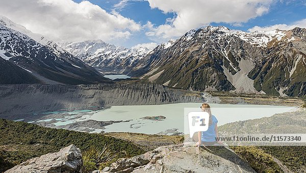 Wanderin sitzt auf Felsen  Ausblick in das Hooker Valley vom Sealy Tarns Track  Gletscherseen Mueller Lake und Hooker Lake  Mount Cook Nationalpark  Canterbury  Südinsel  Neuseeland  Ozeanien