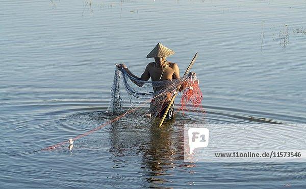 Fishermen with net in Taungthaman Lake  Amarapura  Mandalay  Myanmar  Asia