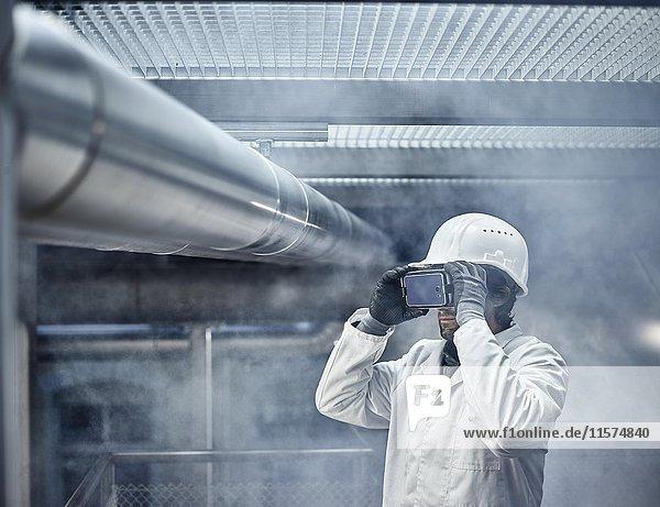Mann mit VR Brille  weißen Helm und Labor Mantel steht vor Industrie-Anlage  Österreich  Europa Mann mit VR Brille, weißen Helm und Labor Mantel steht vor Industrie-Anlage, Österreich, Europa