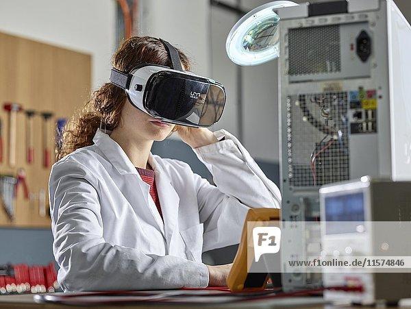Frau mit VR Brille und Labor Mantel sitzt vor geöffnetem PC in einem Elektronik-Labor  Österreich  Europa