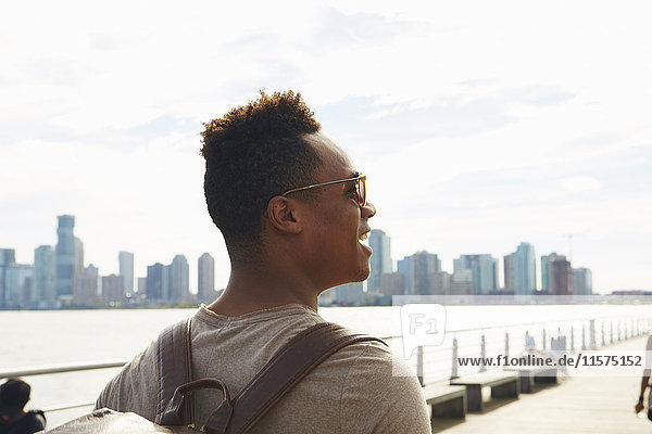 Young man strolling along East river waterfront  New York  USA