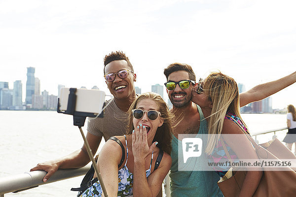 Four adult friends posing for smartphone selfie on waterfront with skyline  New York  USA