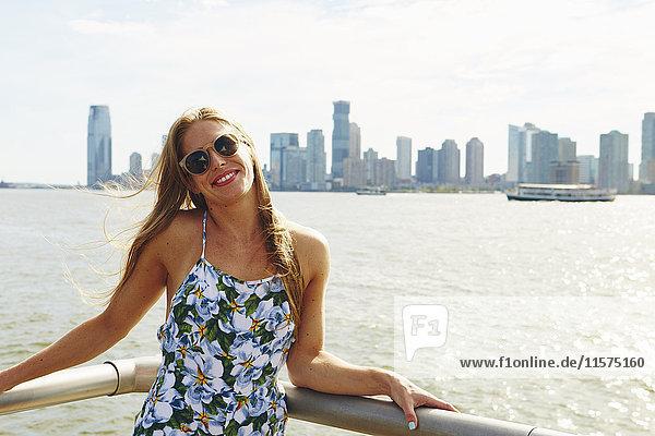 Porträt einer jungen Frau am Skyline-Hafen  New York  USA