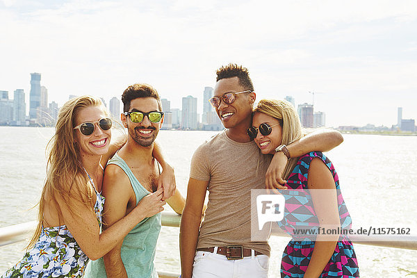 Portrait of four adult friends on waterfront with skyline  New York  USA
