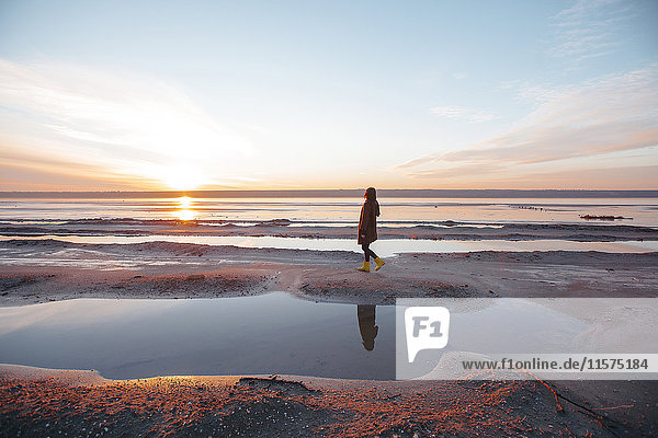 Frau genießt Strand bei Sonnenuntergang