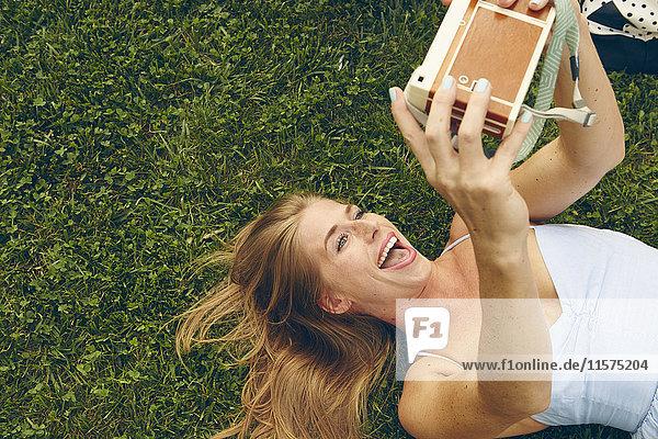 Junge Frau im Gras liegend  die mit einer Retro-Kamera Selfie aufnimmt