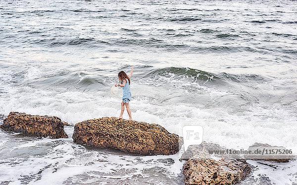 Frau genießt Spaziergang auf Felsen im Meer